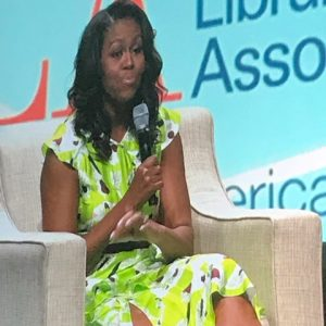 Michelle Obama seated with microphone in hand